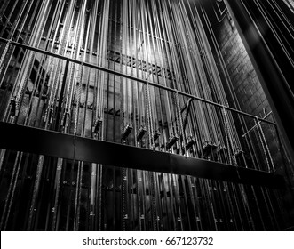Cable and chain rigging backstage in a theater. Vertical lines. Black and white.