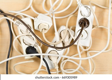 Cable chaos clutter from multiple electric wire extension cords and multi-contact plugs on wooden floor or table background