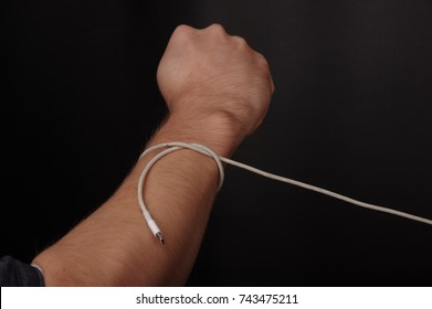 Cable connected to human wrist. Technology Addiction. Concept of Social Disease