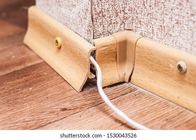 A cable for connecting the Internet is routed through the baseboard. Sloppy work.