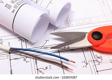 Cable cutter, electric wire and rolls of electrical diagrams lying on construction drawing of house, accessories for engineer jobs