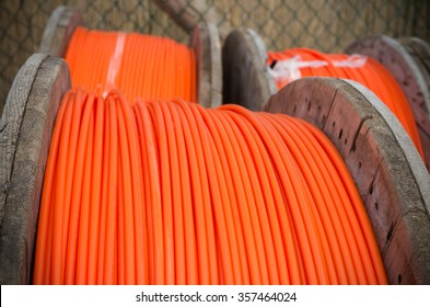 cable drums with orange fiber cable on a construction site