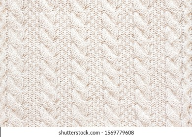 Cable knitting stitch pattern, soft woolen handmade knitted clothes texture.