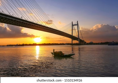 Cable stayed suspension bridge known as the Vidyasagar Setu built on the river Ganges at sunset with view of a boat seen from Princep Ghat at Kolkata, India