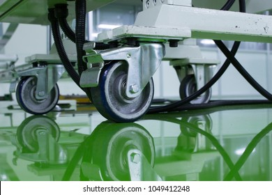 a cable under Table legs on wheels at green epoxy floor.
