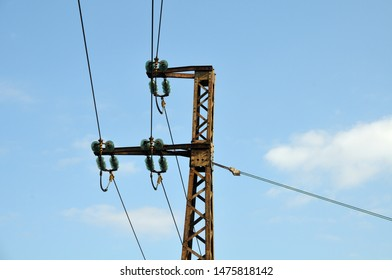 cables and glass disc insulators fixed at rusty metal pylon at a railway station
