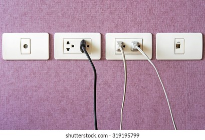 Cables plugged in a white electric outlet mounted on pink wall