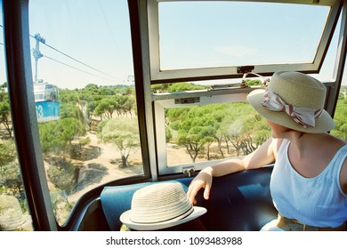 cableway cabin passenger. a woman is riding a cable car