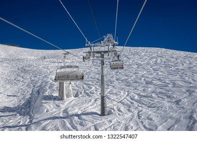 Cableway in motion on rise and descent on background beautiful landscape of snowy field with traces of skiers and snowboarders on the winter resort of Krasnaya Polyana