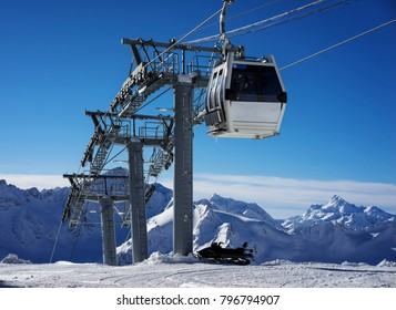 Cableway in motion on rise and descent on background beautiful landscape of snowy high mountains Caucasus Elbrus. Snowmobile is parked at the cable car