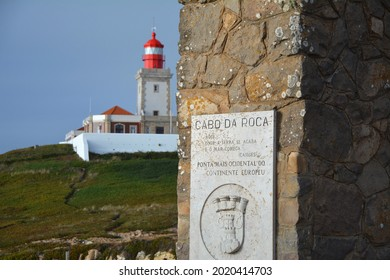 Cabo da Roca, Portugal - 4 July, 2021: Cabo da Roca monument cross board and lighthouse. Cabo da Roca is the most western point of continental Europe in Portugal.