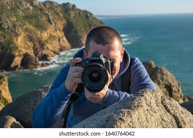 Cabo da Roca, Portugal - February, 2019: A young photographer takes a photo near a cliff against the background of the Atlantic Ocean on a Nikon D810 camera.