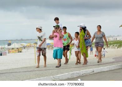 Cabo Frio, Brazil - December 10, 2017: Family walks along the sidewalk of Praia do Forte on a Sunday morning
