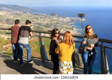 CABO GIRAO, MADEIRA - OCTOBER 11, 2015: Tourists make selfies at the Cabo Girao glass platform, a viewpoint on top of the big cliffs of the island Madeira, on October 11, 2015