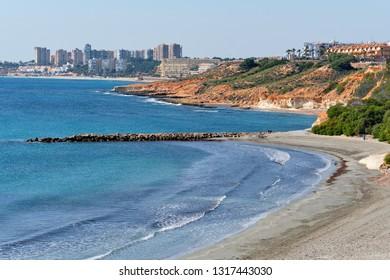 Cabo Roig empty beach and Mediterranean Sea picturesque view, Dehesa de Campoamor highrise buildings skyline, sunny day blue clear sky. Orihuela Costa, Province of Alicante, Costa Blanca, Spain