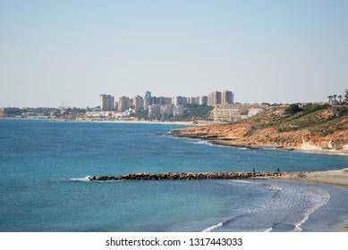 Cabo Roig rocky coastline and Mediterranean Sea picturesque view, Dehesa de Campoamor highrise buildings skyline, sunny day blue clear sky. Orihuela Costa, Province of Alicante, Costa Blanca, Spain