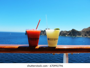Cabo San Lucas/MEX: March 17, 2017 – Frozen colorful alcoholic drinks rest on railing of Norwegian Cruise Line ship as it departs Cabo San Lucas. Blue calm sea and hills and sky are in background.