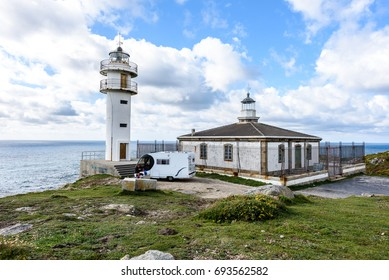 CABO TOURINAN, SPAIN - MAY 17, 2017: Tourists with RV motorhome camper at Cabo Tourinan - the most western point of Spain with lighthouse. Popular tourist and pilgrim destination. Beautiful lighthouse