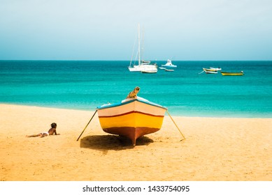 Cabo Verde No Stress. Sunny tropical Sal island vacation background of African child silhouette enjoying sandy Santa Maria beach with colourful boats and turquoise water seascape on Cape verde islands