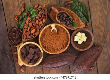 Cacao beans and powder, cacao butter and cacao nibs and chocolate on a wooden background