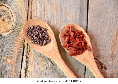 Cacao nibs and acai berries on spoons on wood
