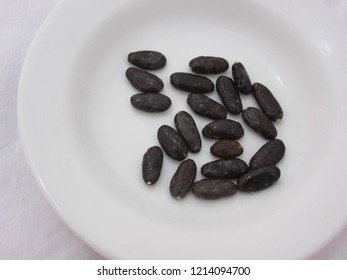 Cacao seeds spread on white plate