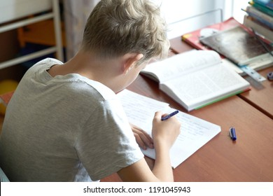 A cacausian blonde teenager boy with bad posture sitting at a table and writing in a copybook. Slouching blonde teenager boy doing school homework.