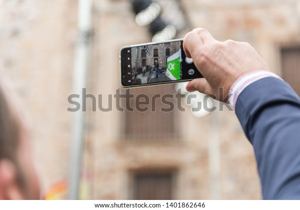 Caceres, Extremadura, Spain - May 18, 2019: A man takes a photograph of the intervention of the leader of the extreme right-wing Vox party, Santiago Abascal, at the rally held in the Plaza de San
