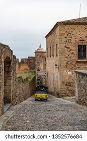Caceres, Caceres, Spain - February 10, 2019: A yellow tourist tuc tuc goes down one of the slopes of the old town of Caceres, Extremadura, Spain.