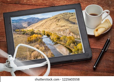 Cache la Poudre River at a canyon mouth above Fort Collins, Colorado in a  fall scenery, reviewing an aerial image on a digital tablet