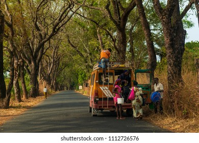 Cacheu, Republic of Guinea-Bissau - February 1, 2018: People entering an old public mini bus in the outskirts of the city of Cacheu, in Guinea Bissau.