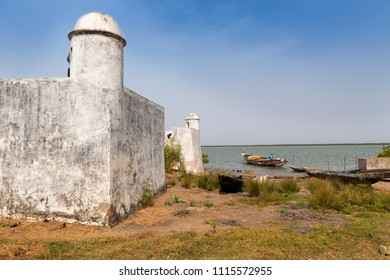 Cacheu, Republic of Guinea-Bissau - February 1, 2018: Detail of the Cacheu Fortress and a fisherman preparing his canoe in the port of the city of Cacheu, in Guinea Bissau.