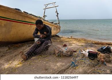 Cacheu, Republic of Guinea-Bissau - February 1, 2018: Fisherman repairing fishing nets in the port of the city of Cacheu, in Guinea Bissau.