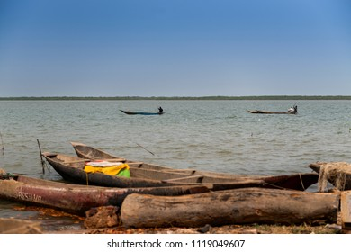 Cacheu, Republic of Guinea-Bissau - February 1, 2018: Fishermen on their canoes in the Cacheu River near the city of Cacheu, in Guinea Bissau.