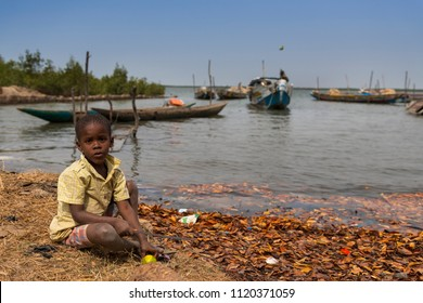 Cacheu, Republic of Guinea-Bissau - February 1, 2018: Young boy playing next to the water in the port of the city of Cacheu, in Guinea Bissau.