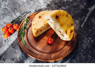 Caciotta with sun dried tomatoes cheese. Healthy rustic food. Dairy milk products, upmarket concept. Variety of vegetables around