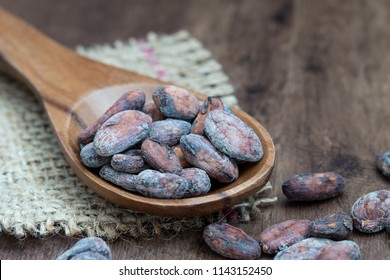 cacoa beens on a wooden spoon