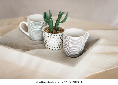 Cactus in a mug. A tray with mugs on the table. Interior details. Hugge.