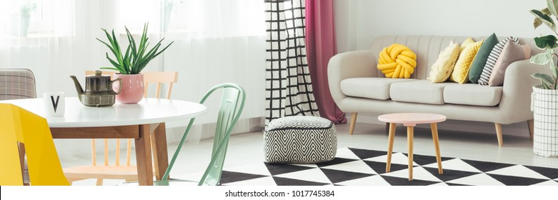 Cactus in pink pot and kettle on white round table in warm living room interior with yellow cushions on sofa, wooden stool and pouf on the carpet