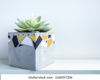 Cactus pot. Beautiful painted concrete pot. Green succulent plant in modern cubic concrete planter on white wooden shelf on white wall background with copy space.