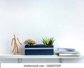 Cactus pot. Beautiful painted concrete pot. Green succulent plant and flower in modern concrete planter with books and wooden figure on white wooden shelf on white wall background with copy space.
