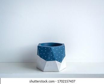 Cactus pot. Concrete pot. Empty blue painted modern geometric concrete planter on white wooden shelf isolated on white background.