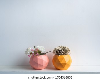 Cactus pot. Concrete pot. Pink and orange modern geometric concrete planters with blooming flower on white wooden shelf isolated on white background.