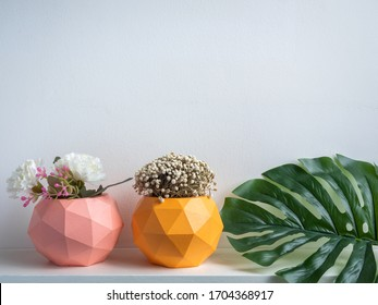 Cactus pot. Concrete pot. Pink and orange modern geometric concrete planters with flower and green palm leaf on white wooden shelf isolated on white background.