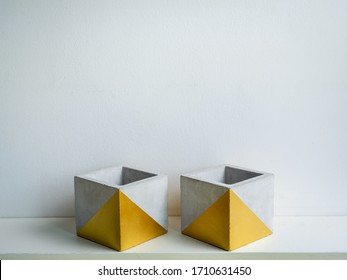 Cactus pot. Concrete pot. Two empty modern geometric concrete planters with gold painted on white wooden shelf isolated on white wall background.