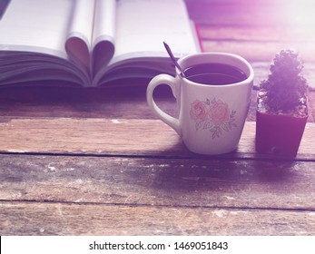 Cactus in small pots,White mug and blurred Book page rolls,like shaped heart on old wood plank,soft dark tone,dimly light,with lens flare,free space for your text design or your products.