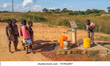 CACUSO, ANGOLA - MAY 06 2014: Unidentified local African children pumping drinking water at well built by charity organization, Southern Africa