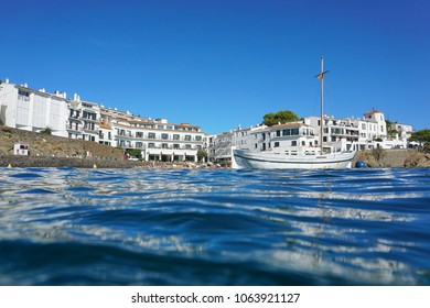 Cadaques seaside village coastline with a traditional boat seen from water surface, Mediterranean sea, Costa Brava, Catalonia, Spain