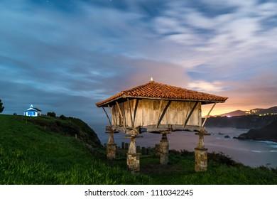 CADAVEDO, ASTURIAS, SPAIN, September 30, 2017. Hórreo and hermitage Santa María de Riégala (La Regalina)located in the background on the Asturian coast in northern Spain.