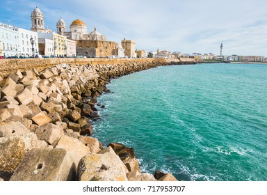 Cadiz embankment panorama in Spain with beautiful cathedral, big breakwater stones and Atlantic ocean waters with soft focus